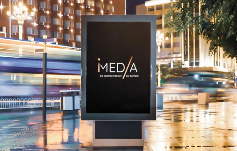 photo d'une affiche en pleine rue et de nuit avec le logo I-Media communication digitale à Rouen