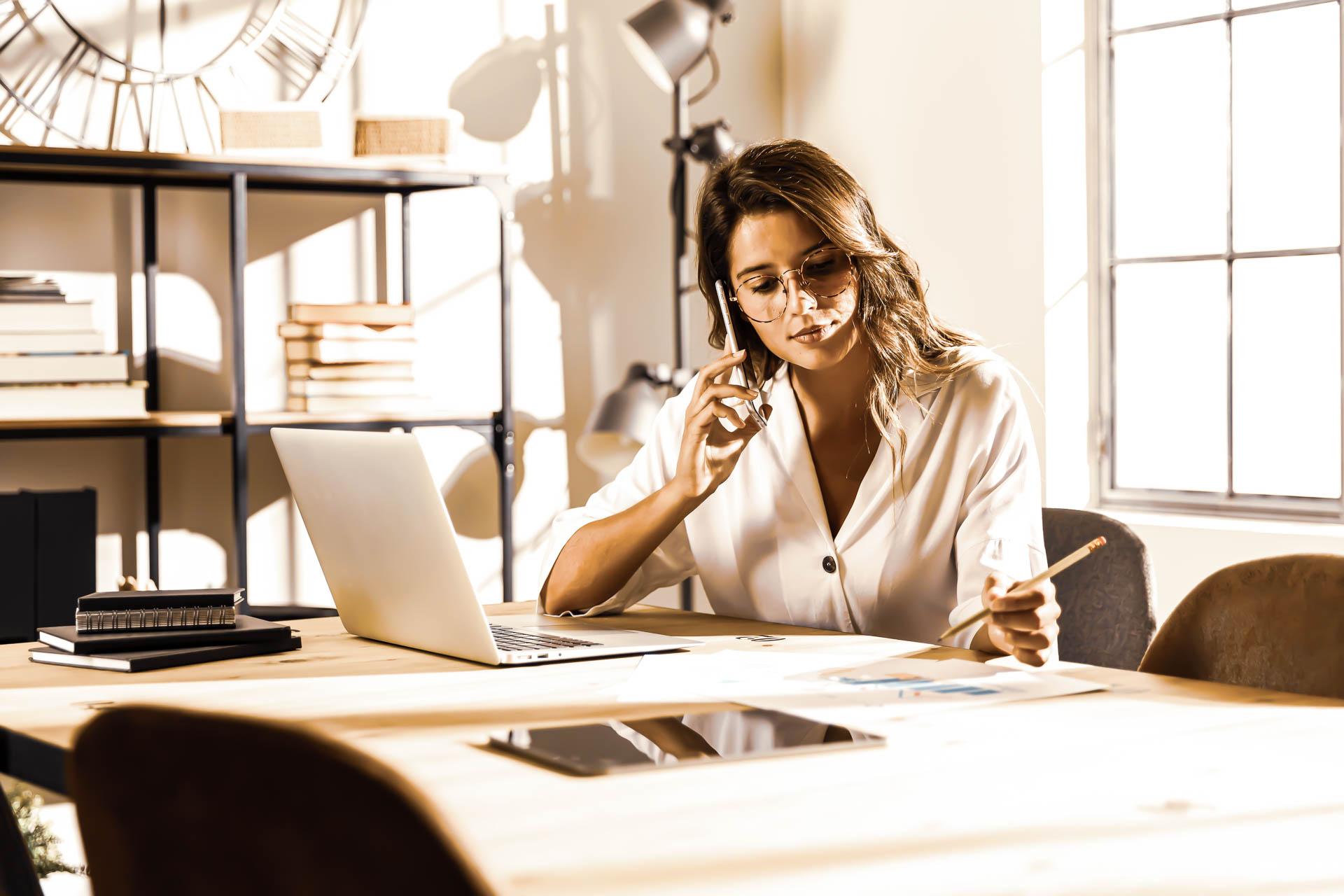 femme au téléphone pour représenter le pôle commercial d'i-media, agence digitale