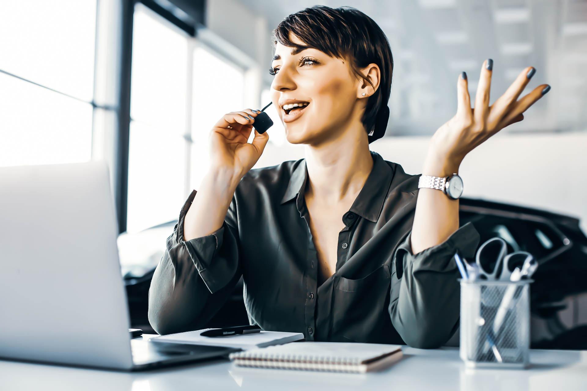 femme au téléphone face à son ordinateur pour représenter le pôle support d'i-media