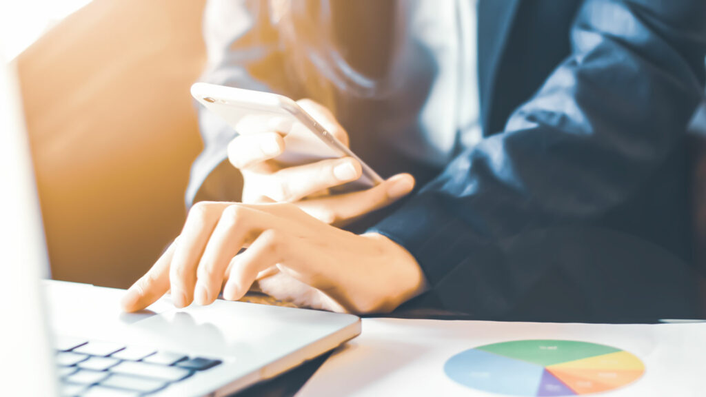 une femme sur un ordinateur avec son portable pour mettre en avant les références i-media